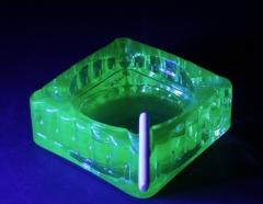 Vaseline/Uraniium glass ashtray with candy cigarette lit by black light